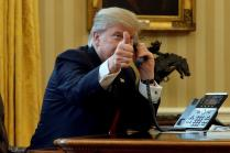 U.S. President Donald Trump gives a thumbs-up to reporters as he waits to speak by phone with Saudi Arabia's King Salman in the Oval Office at the White House in Washington, U.S., January 29, 2017. REUTERS/Jonathan Ernst/File Photo